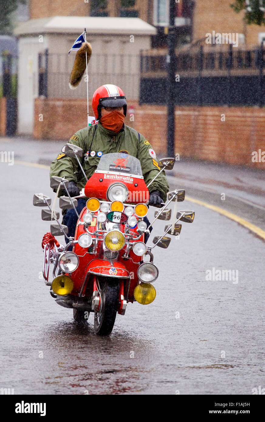 A mod riding a scooter with lots of mirrors and a fox tail attached to the aerial in a rain storm during a scooter - Stock Image