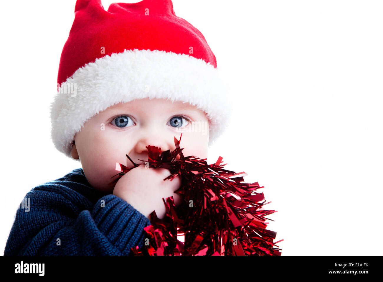 A studio shot of young child against a plain white background wearing a Christmas hat and holding tinsel - Stock Image