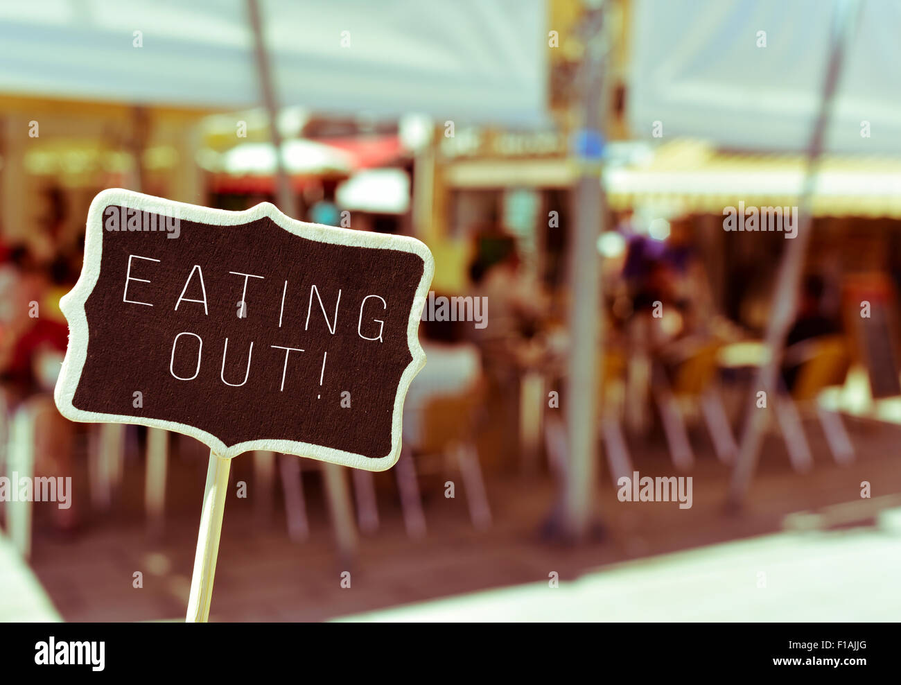 closeup of a chalkboard with the text eating out, in the busy terrace of a restaurant - Stock Image