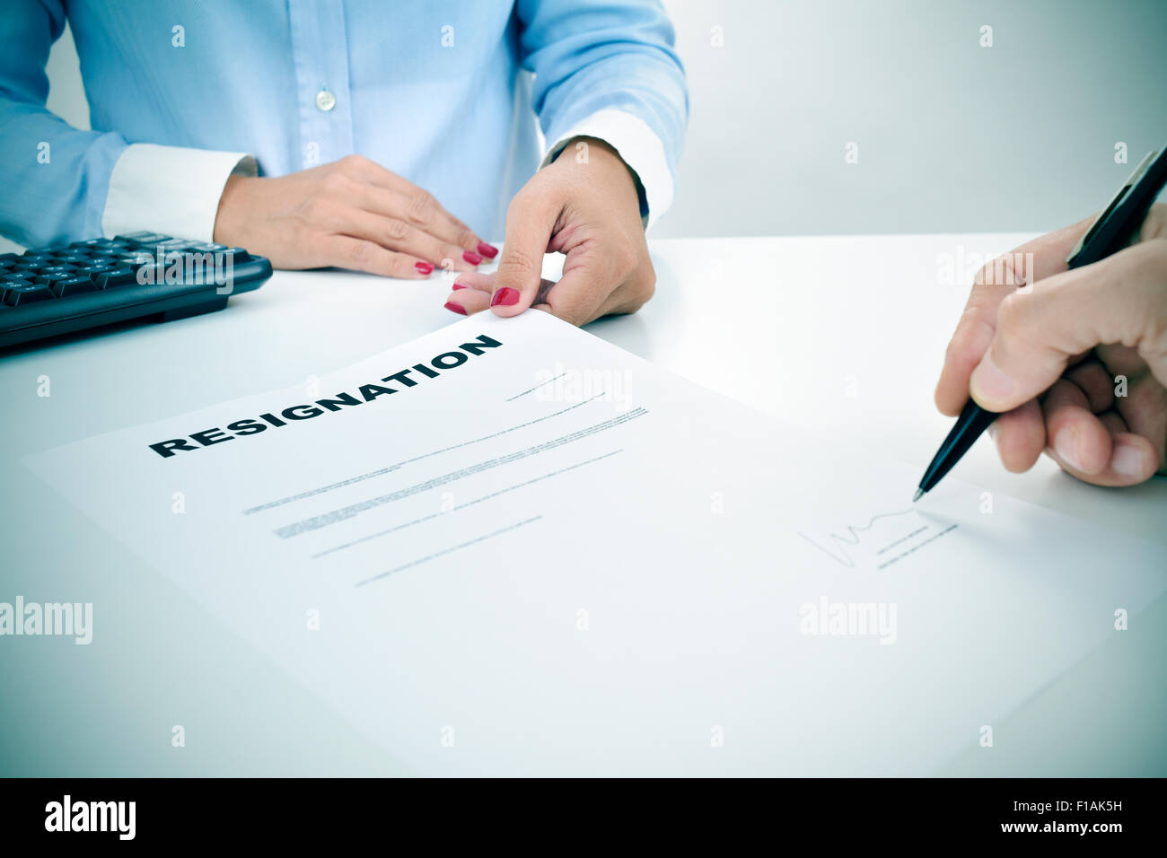 closeup of the hand of a man who is signing a resignation document on a desk in front of a young woman - Stock Image