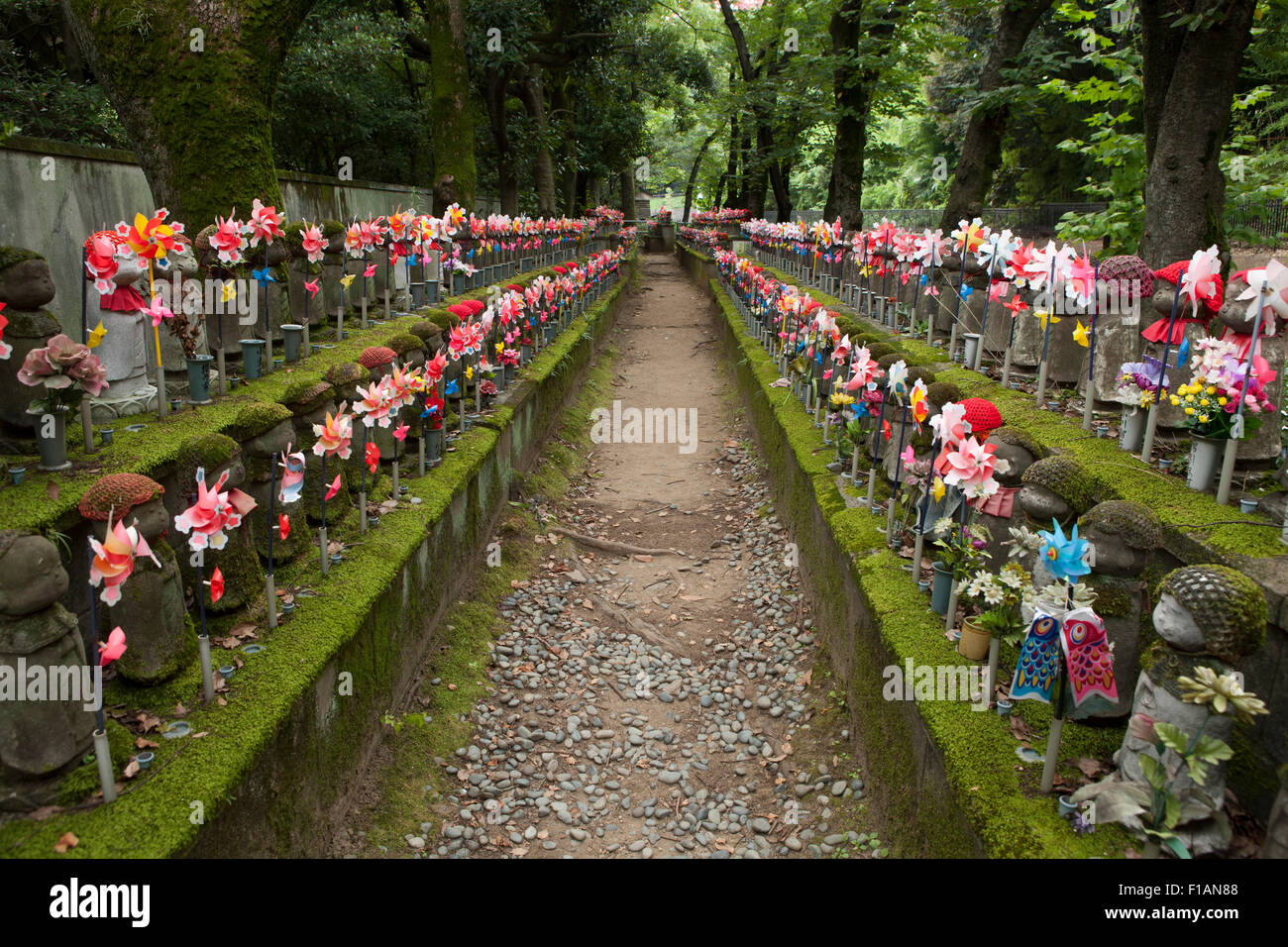 Japan, Tokyo, Jizo statues decorated with bibs, knitted caps, flowers and pinwheels at Zojoji temple - Stock Image