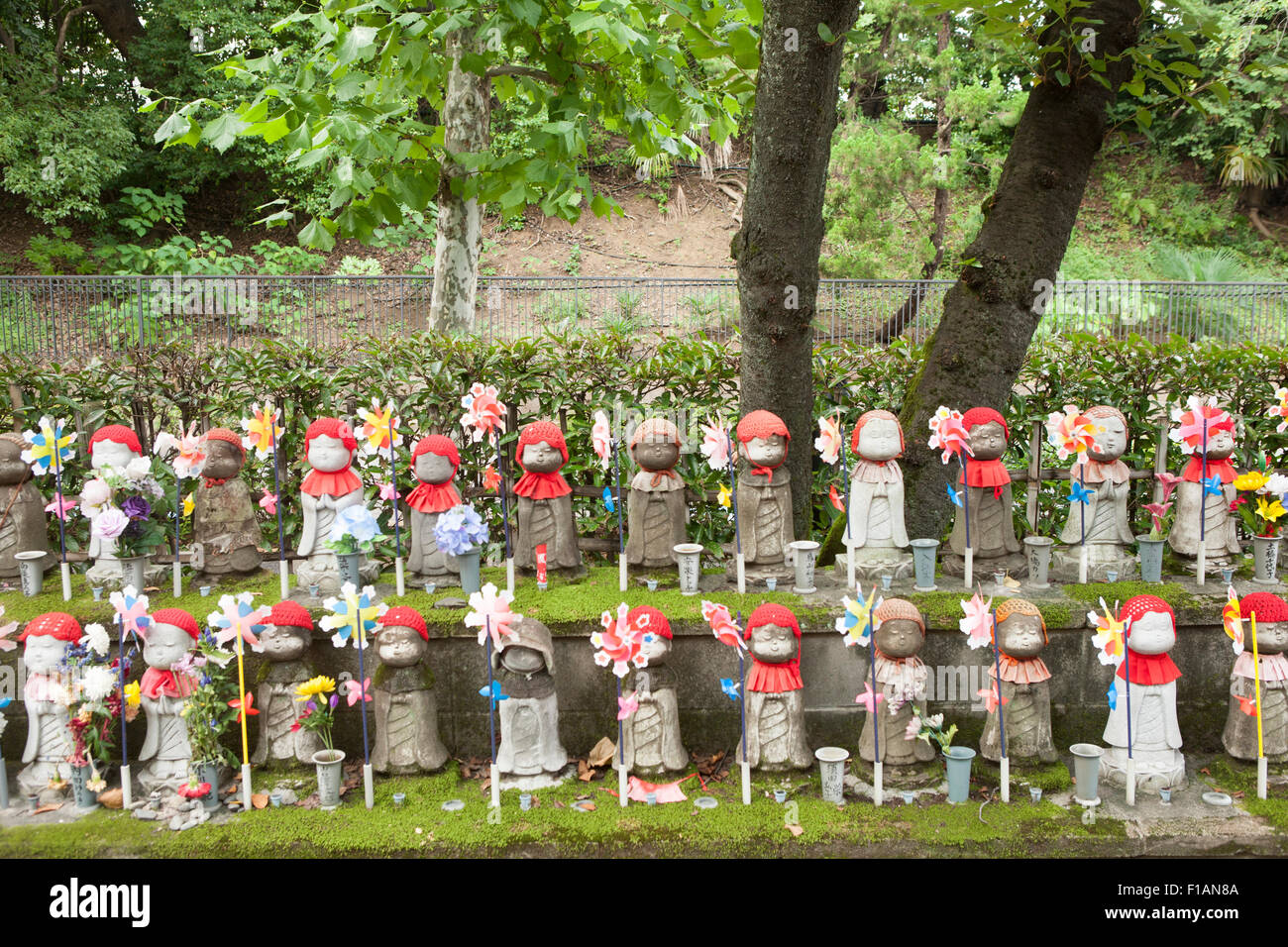 Japan, Tokyo, rows of Jizo statues decorated with bibs, knitted caps, flowers and pinwheels at Zojoji temple - Stock Image