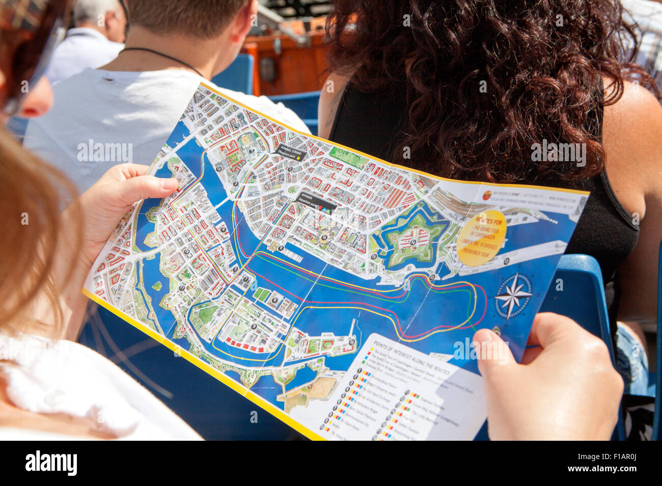 Female tourist reading a map of Nyhavn waterfront, canal and entertainment district in Copenhagen, Denmark - Stock Image