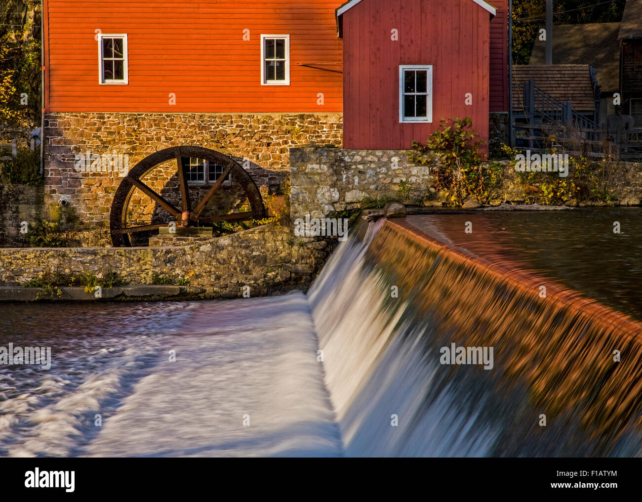 The historic Red Mill, gristmill, vintage water wheel and the Raritan River Damn in Clinton, New Jersey, USA, pov - Stock Image
