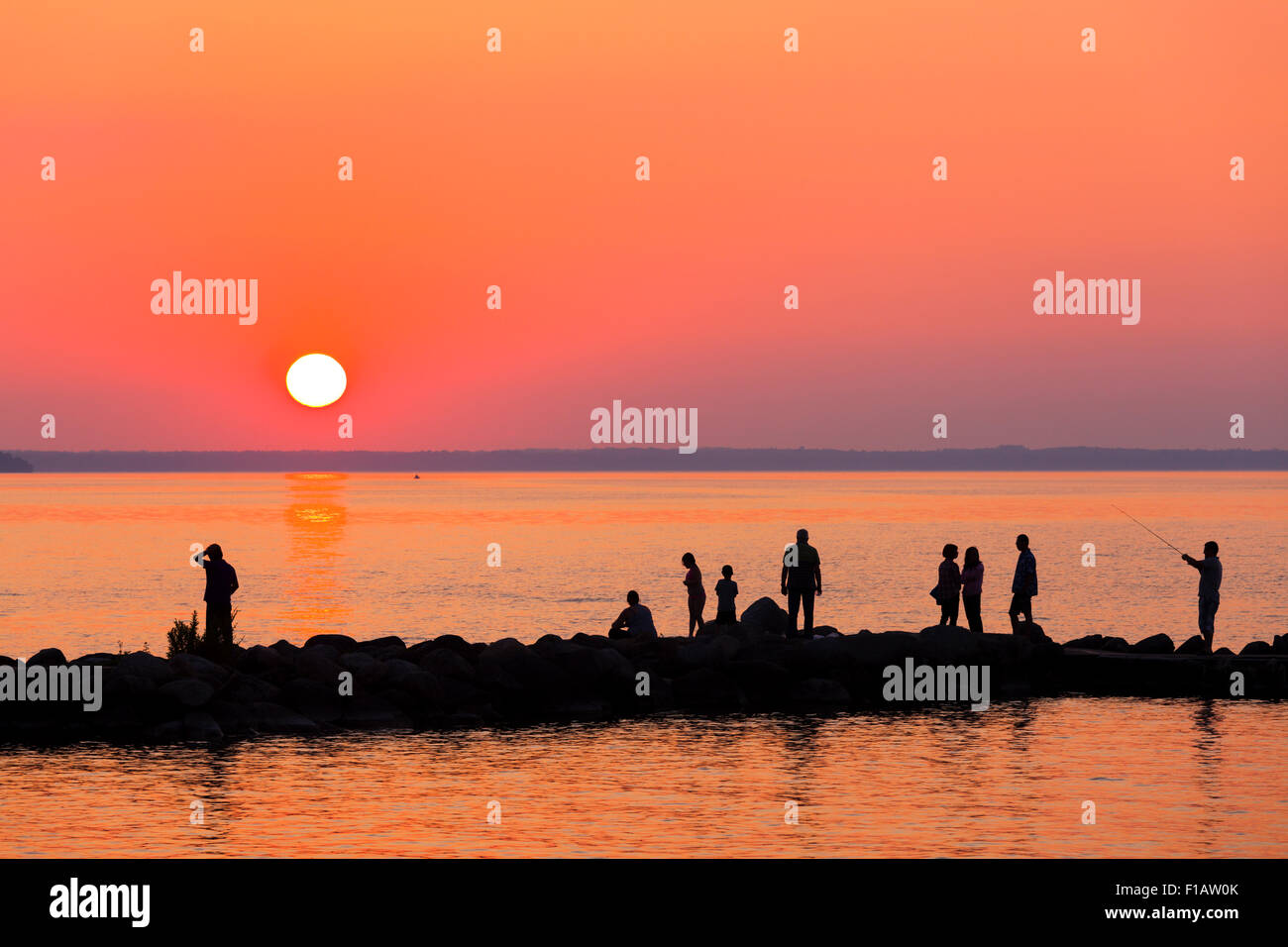 Willow Beach Ontario >> People Silhouetted Against A Vibrant Sky As The Sun Sets Over Lake