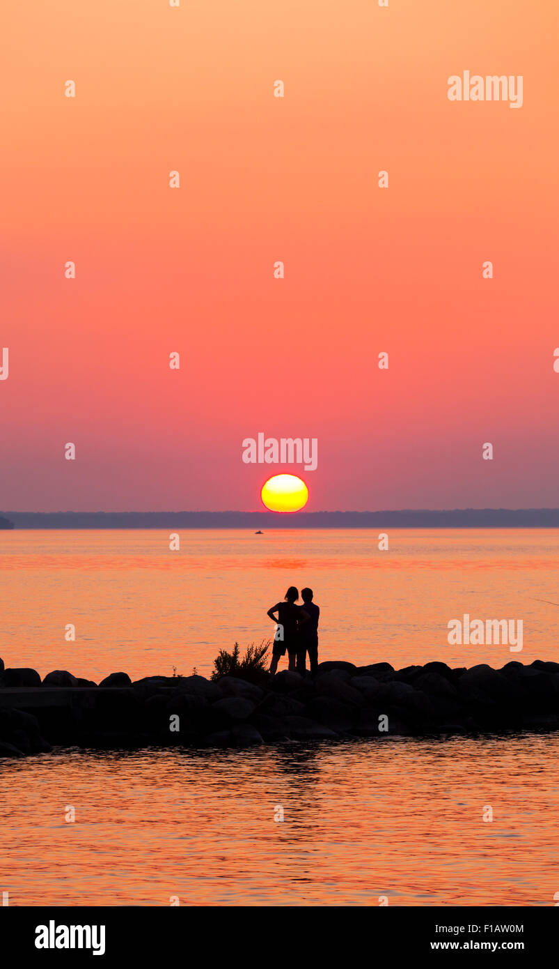 Willow Beach Ontario >> People Silhouetted Against A Vibrant Sky As The Sun Sets