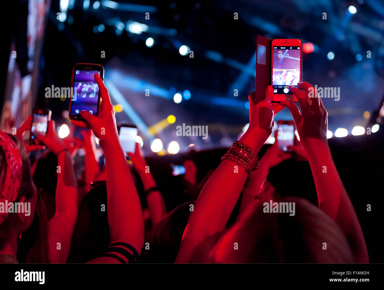Hands holding up cell phones at a music concert - Stock Image