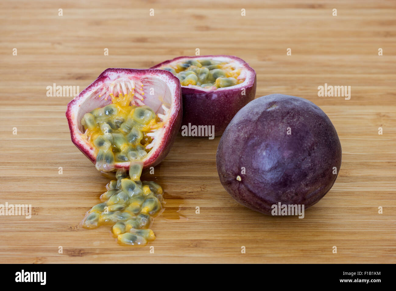 Close-up of a whole and split passion fruits (passionfruit, purple granadilla (Passiflora edulis)), seeds on a wooden - Stock Image