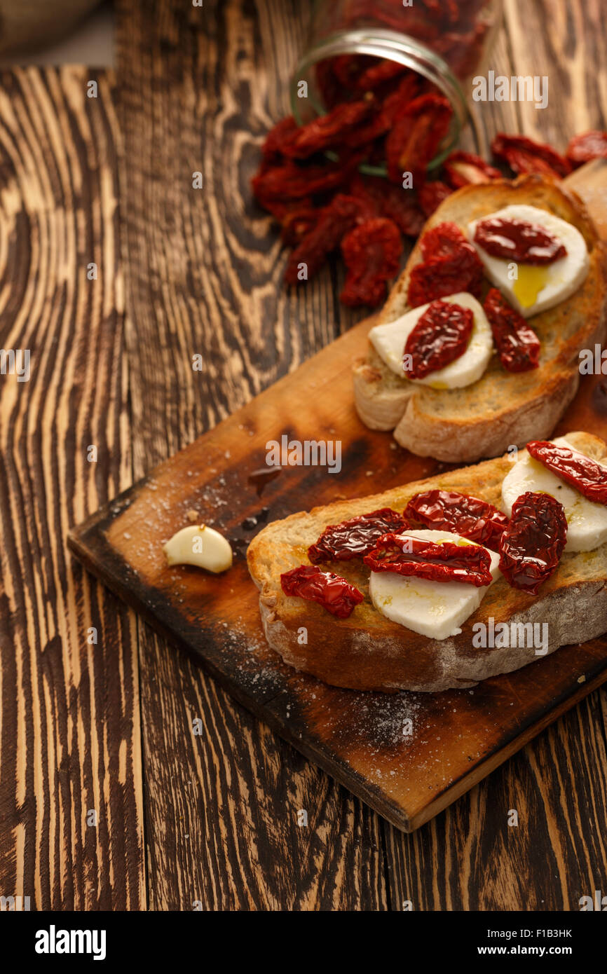 Bruschetta with dried tomatoes, mozzarella, garlic and olive oil. Traditional Italian cuisine sandwich made of grilled - Stock Image