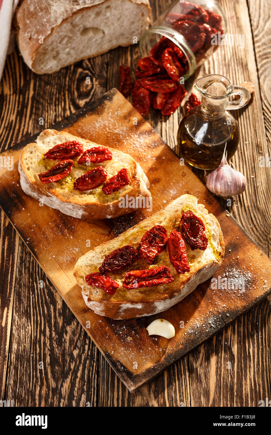 Bruschetta with dried tomatoes, garlic and olive oil. Traditional Italian cuisine sandwich made of grilled ciabatta. - Stock Image