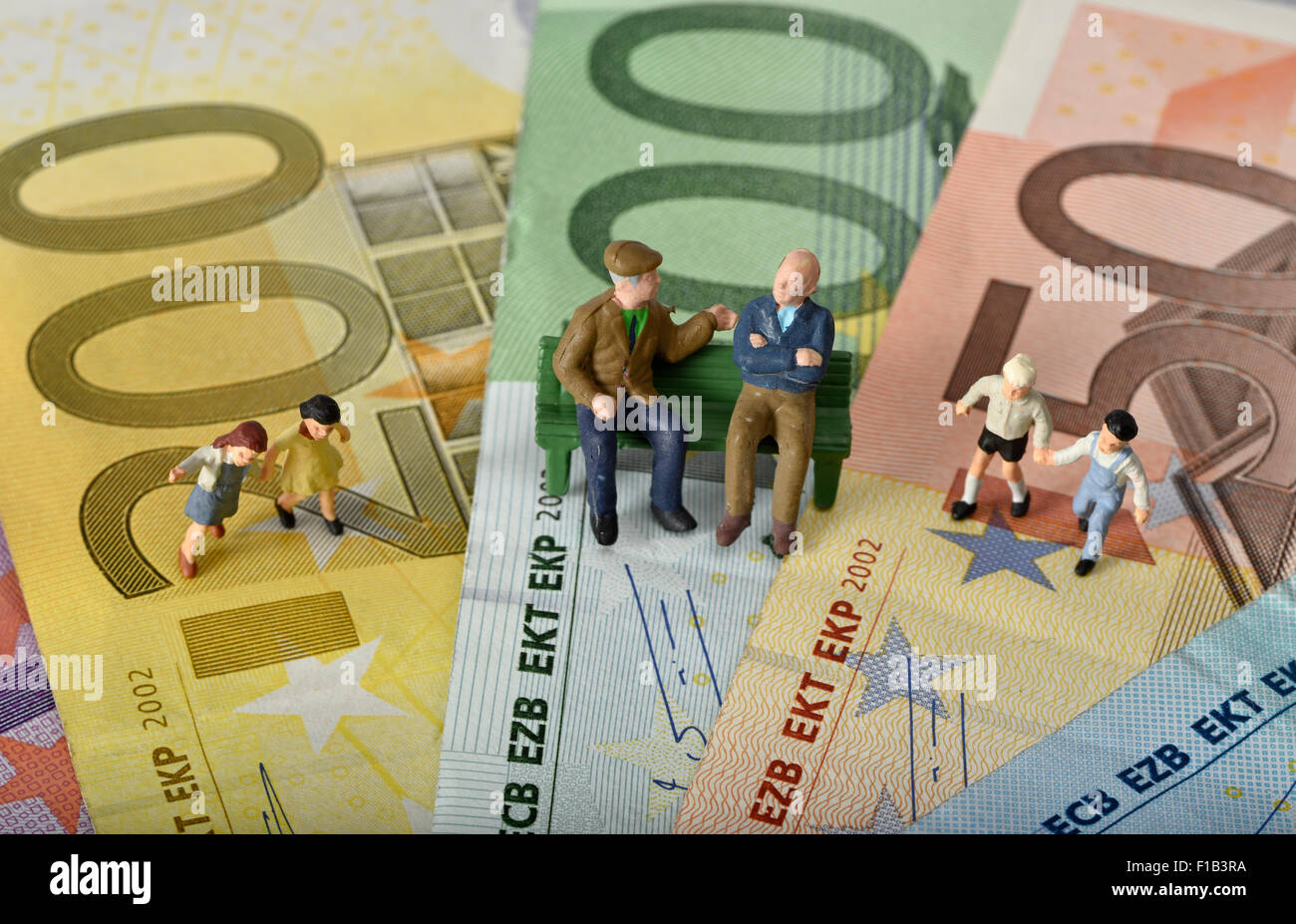 Old people sitting on a bench, with children, euro banknotes, symbol for generations, retirement, pension Stock Photo