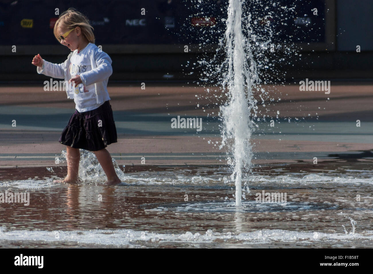 Girl playing in the fountain near the O2 arena, North Greenwich, London, England, United KingdomStock Photo