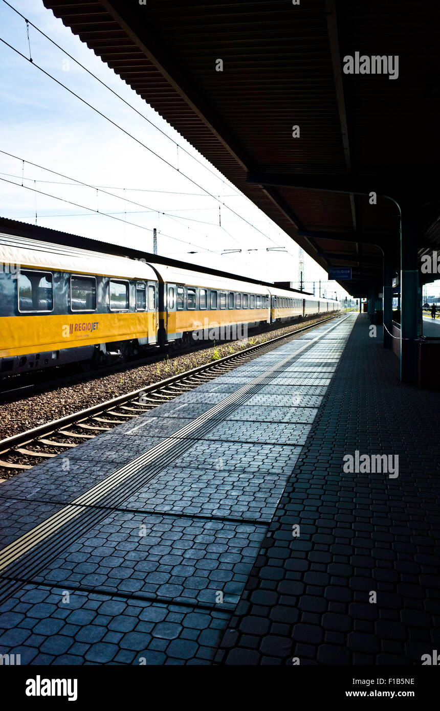 railway platform and a train waiting to leave - Stock Image