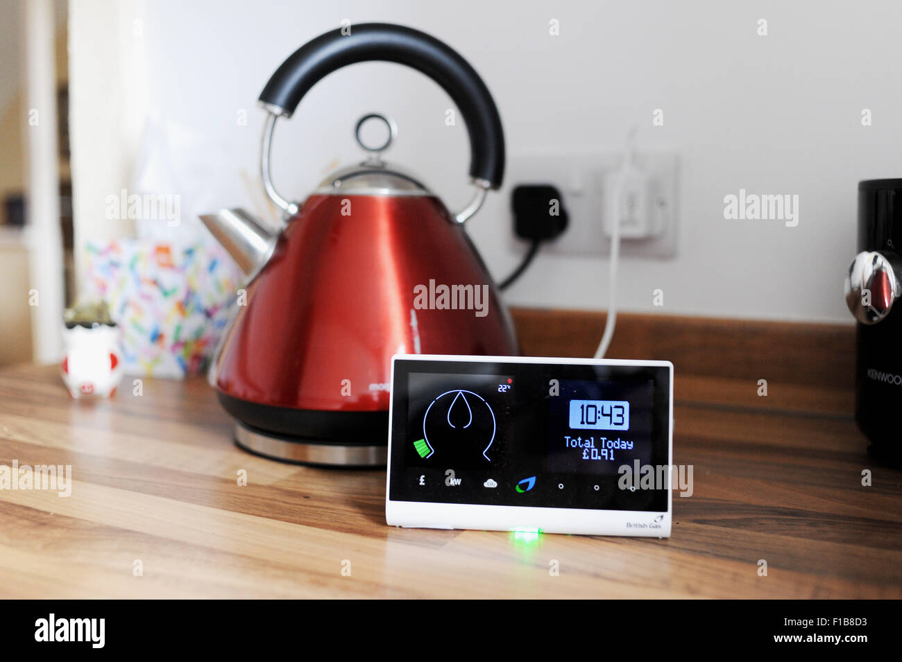 British Gas smart meter showing consumption of electricity and gas used with domestic appliance a kettle in the - Stock Image