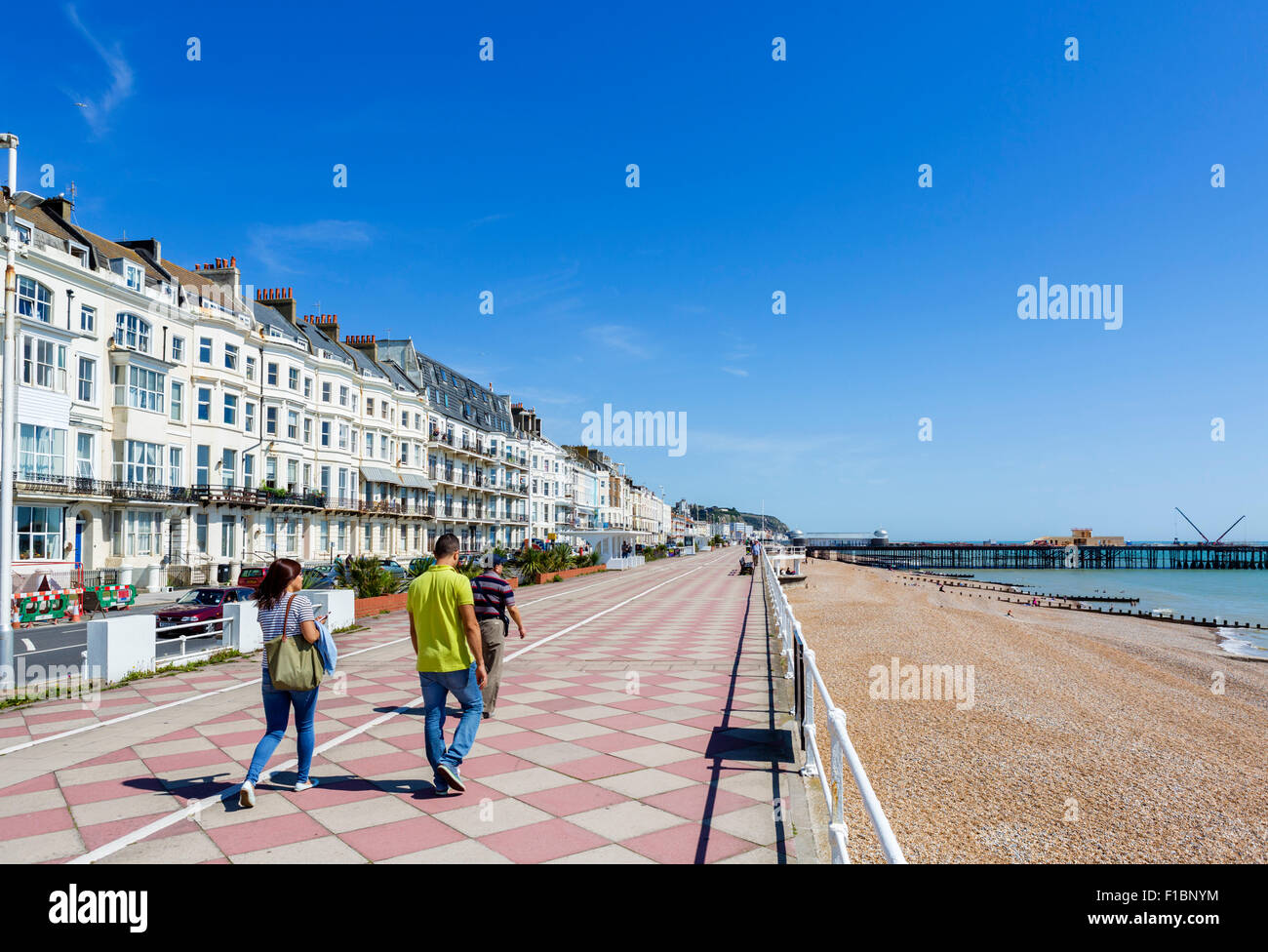 The seafront promenade and beach with the burnt out pier in the distance, Hastings, East Sussex England, UK - Stock Image