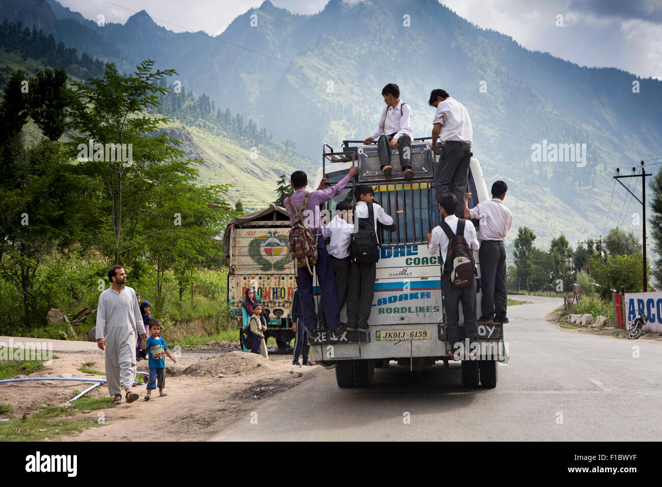 India, Jammu & Kashmir, Srinagar to Leh Highway, school children clinging to back of overloaded bus - Stock Image