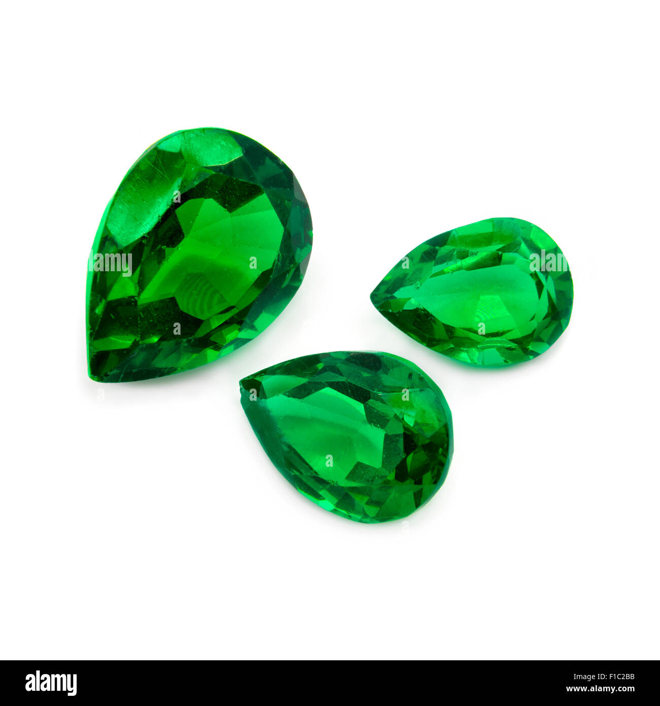 Green emeralds on a white background. Precious gems. - Stock Image
