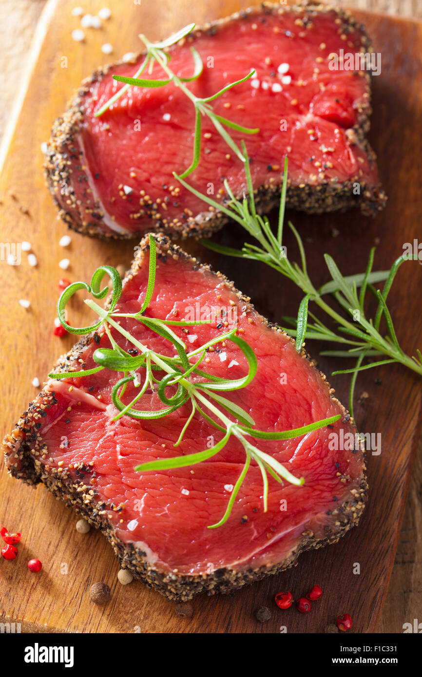 raw beef steak with spices and rosemary on wooden background - Stock Image