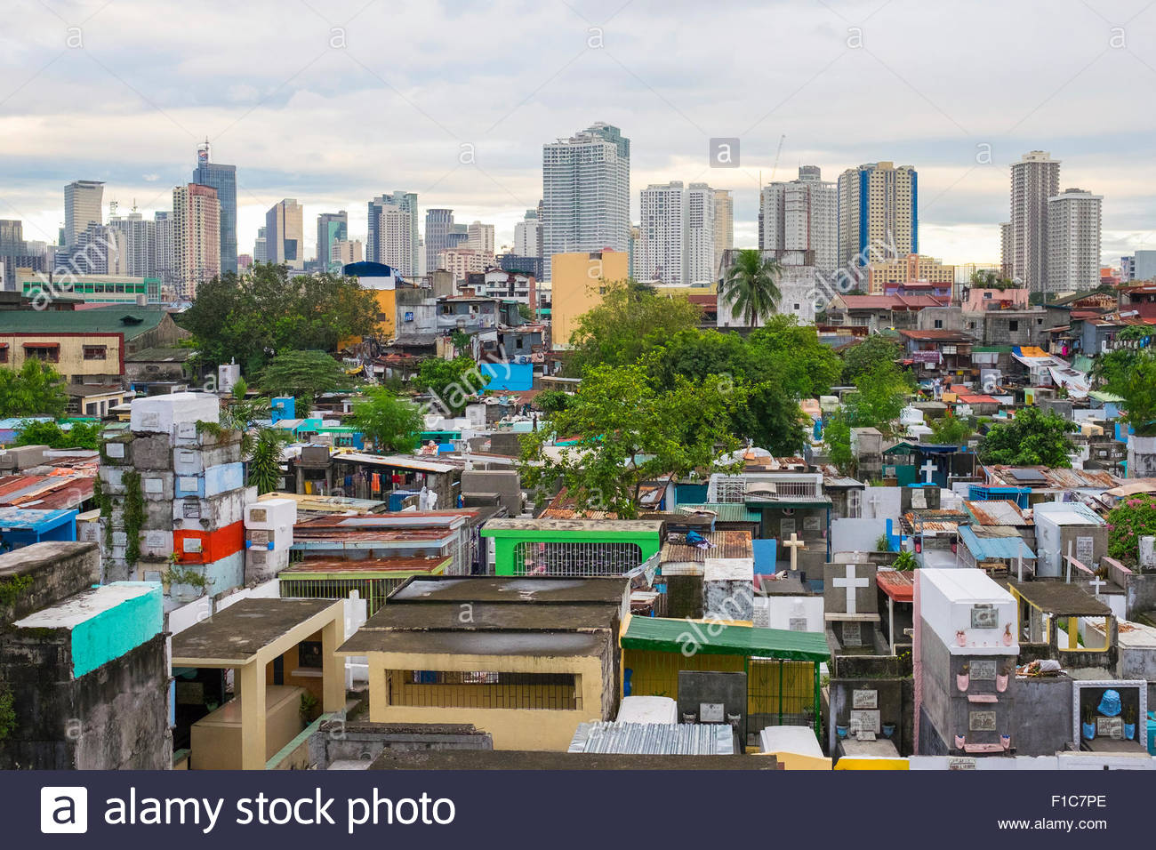 Towers of Makati City financial district above Pasay City Cemetary, Manila, National Capital Region, Philippines - Stock Image