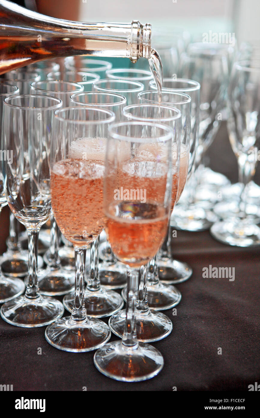 Pink champagne being poured into champagne flutes - Stock Image