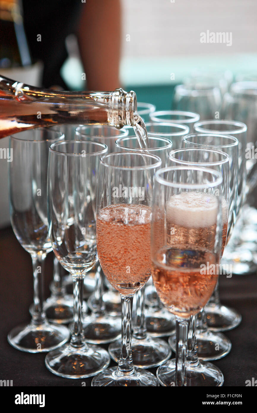 Pink champagne being poured in champagne glasses - Stock Image
