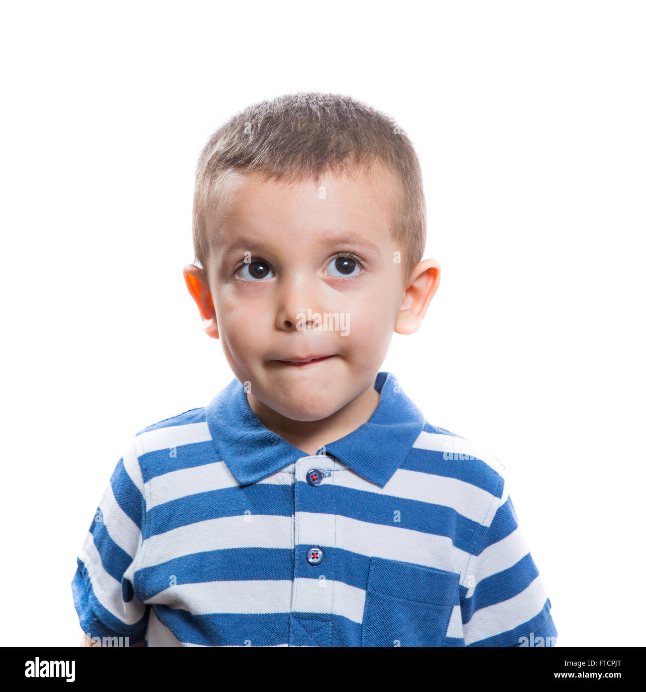 Portrait of dubious beautiful little boy isolated on white background - Stock Image