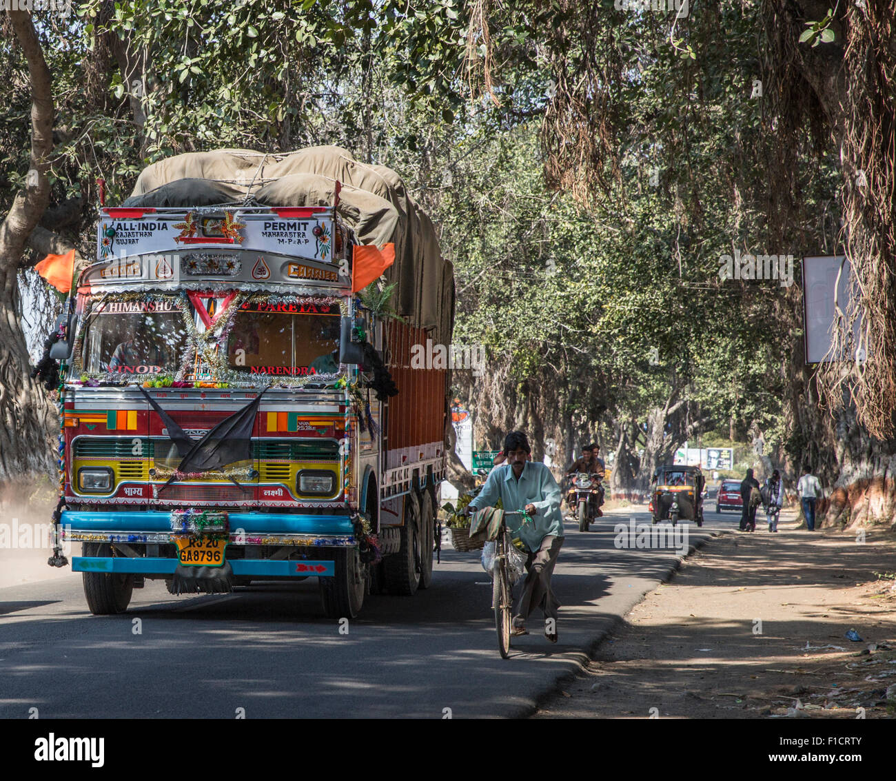 Long haul truck with typical gaudy decorations churns up dust on the main road from Ellora Caves to Aurangabad, - Stock Image