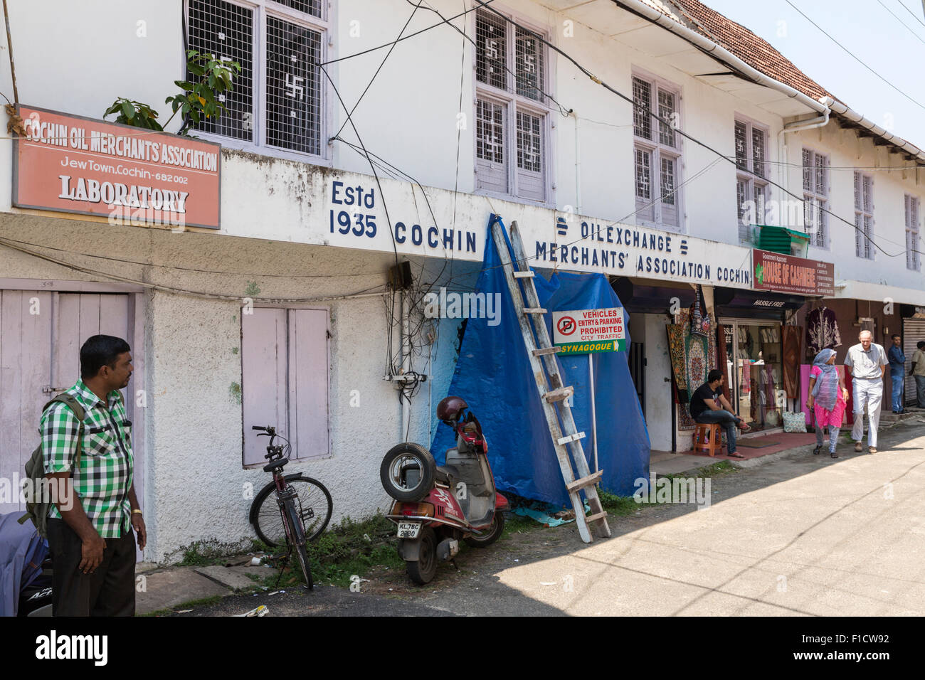 Warehouse building and pedestrians in Jew Town, Kochi, India. Note the Hindu swastikas decorating the window grilles - Stock Image
