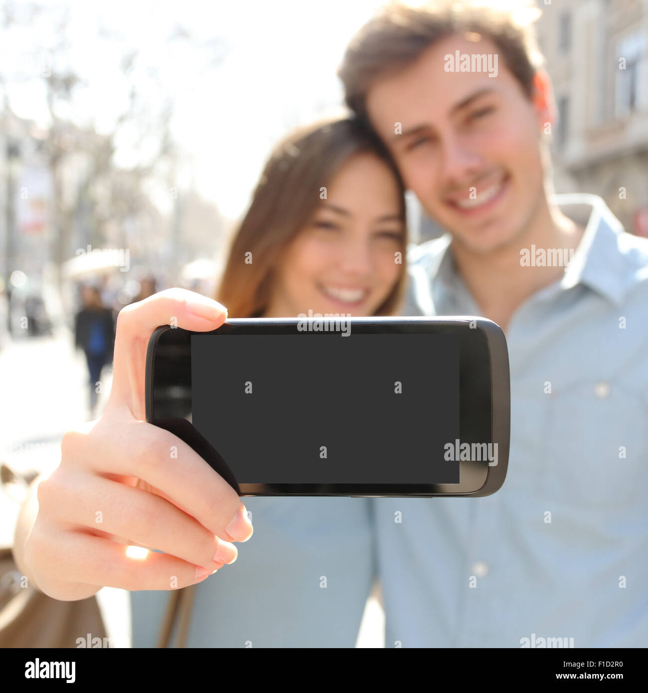 Happy couple or friends making a selfie photo with a smart phone and showing a blank screen to the camera - Stock Image