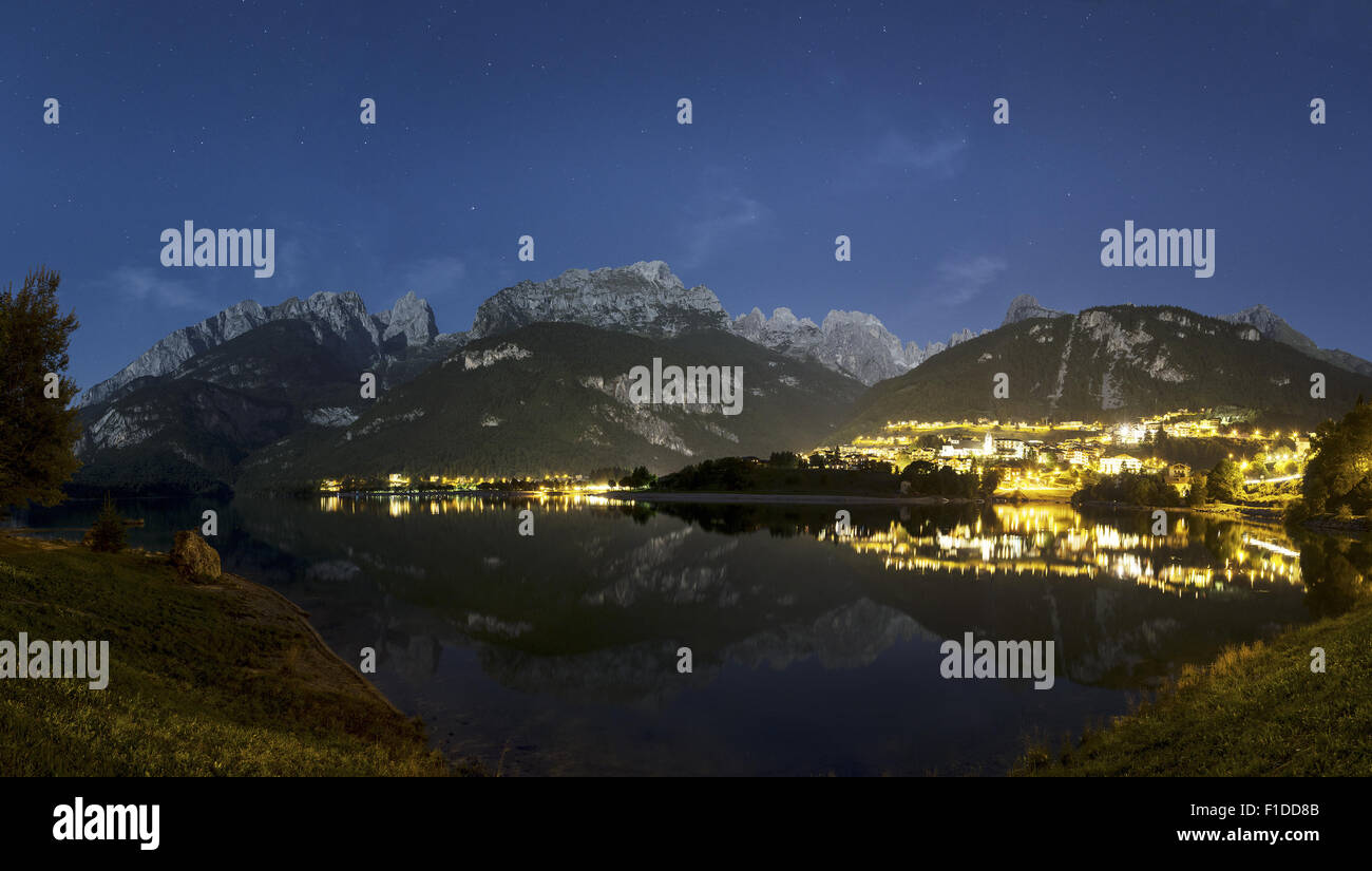 Night landscape on the Moveno lake and city with Dolomiti of Brenta Group in background at the moonlight - Stock Image