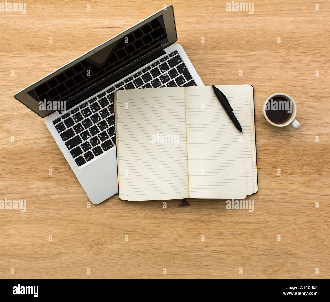 Laptop, Notepad and coffee Cup top view on wooden table texture. - Stock Image