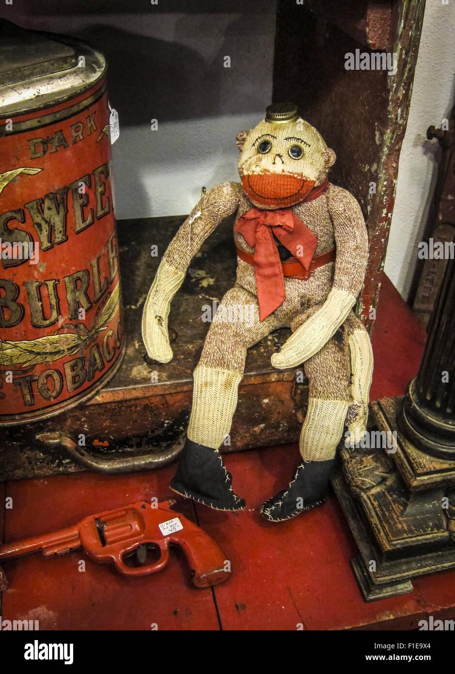 Vintage handicraft sock monkey in antique store - Stock Image