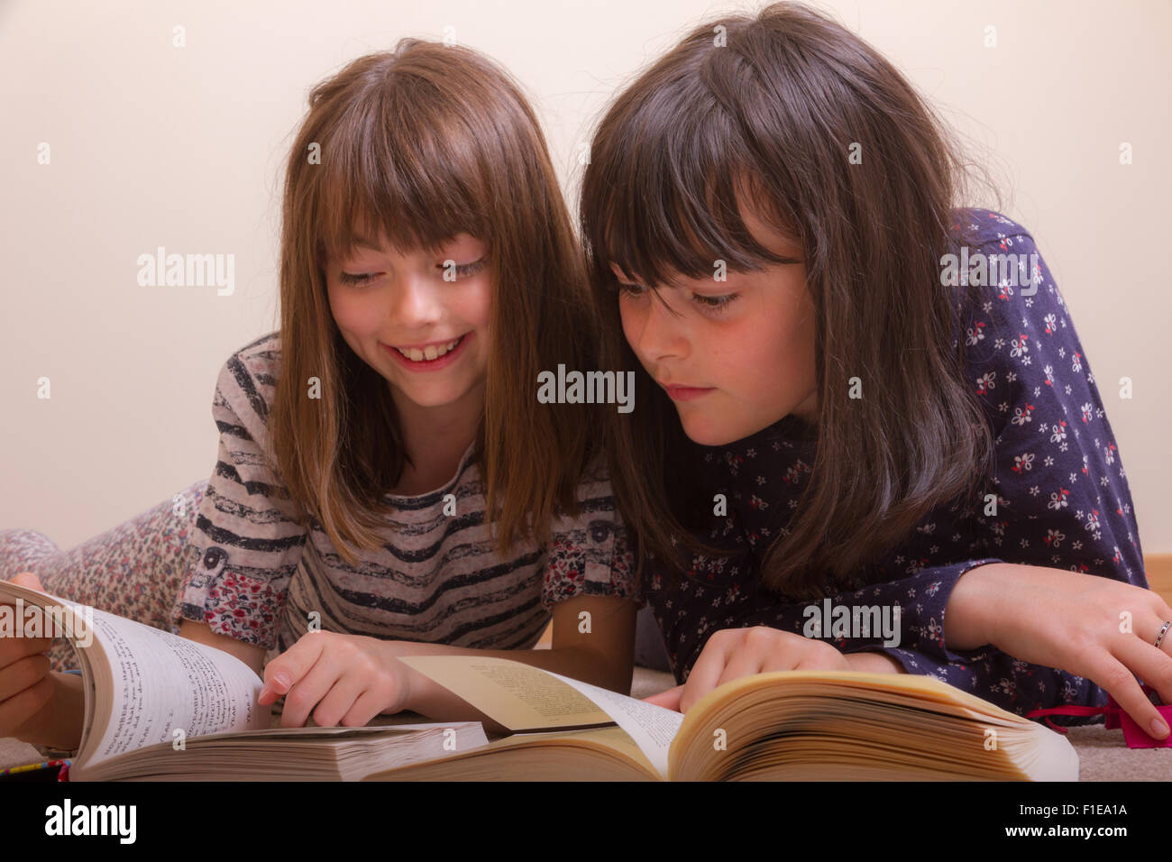 2 young white 9 & 11 year old girls on the floor reading books as one smiles and points to something funny in - Stock Image