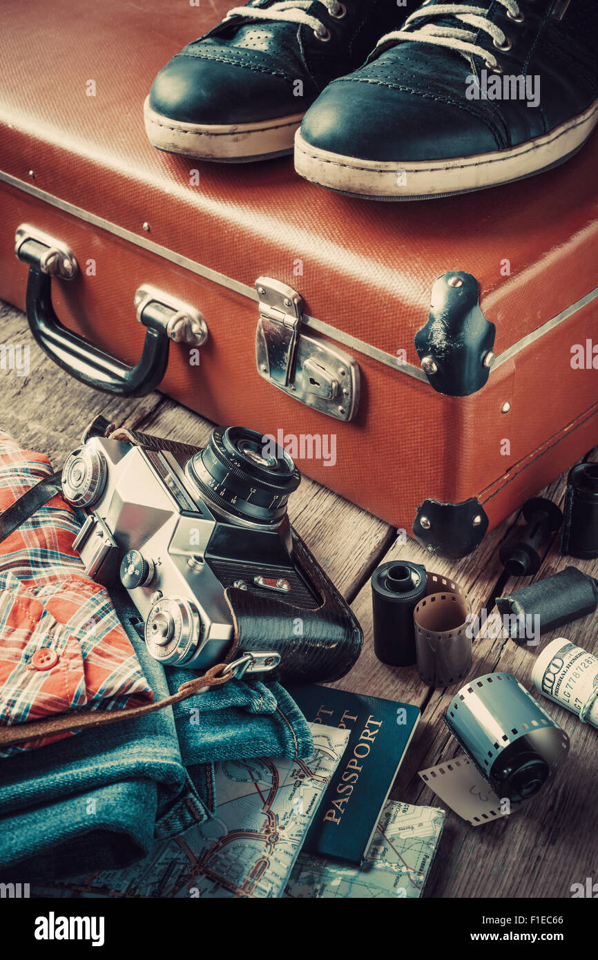 Old travel suitcase, sneakers, clothing, map, filmstrip and retro film camera. Vintage stylized. - Stock Image
