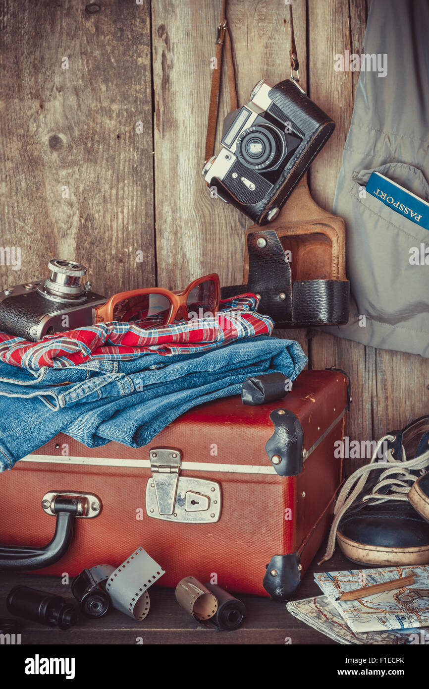 Old travel suitcase, sneakers, clothing, sunglasses, maps, filmstrip and retro film camera . Vintage stylized. - Stock Image