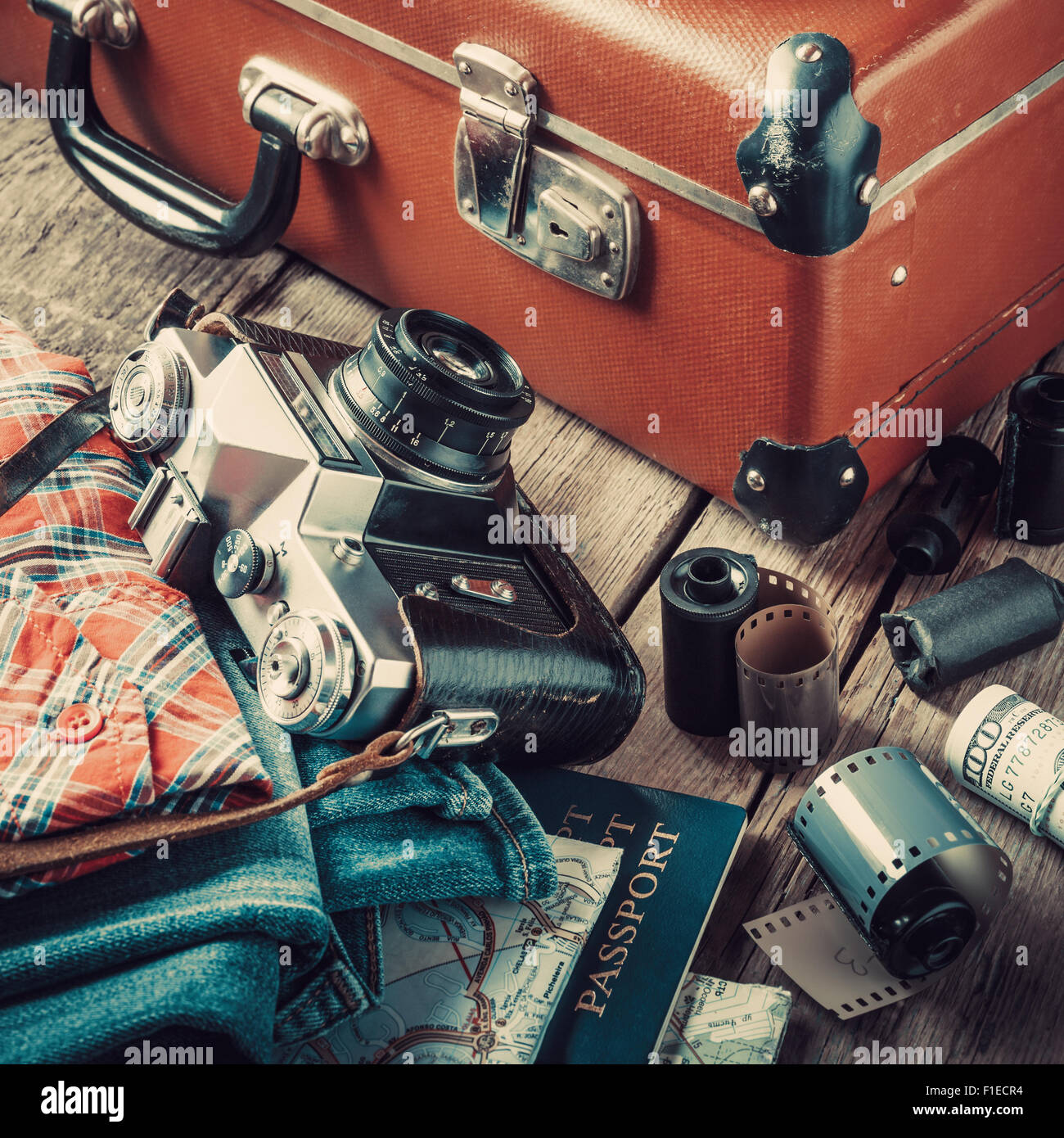 Old travel suitcase, clothing, map, filmstrip and retro film camera on wooden background. Vintage stylized. - Stock Image