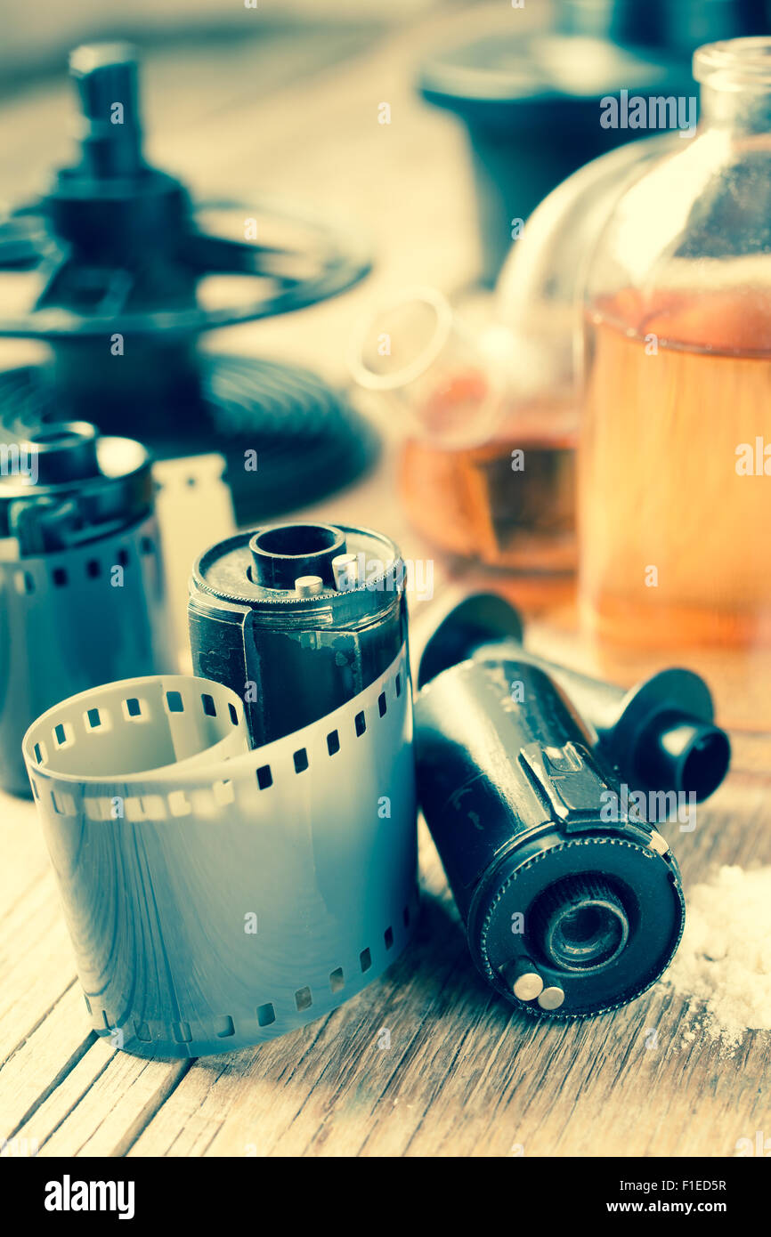 Old photo film rolls, cassette and photographic equipment on desk. Vintage stylized. - Stock Image
