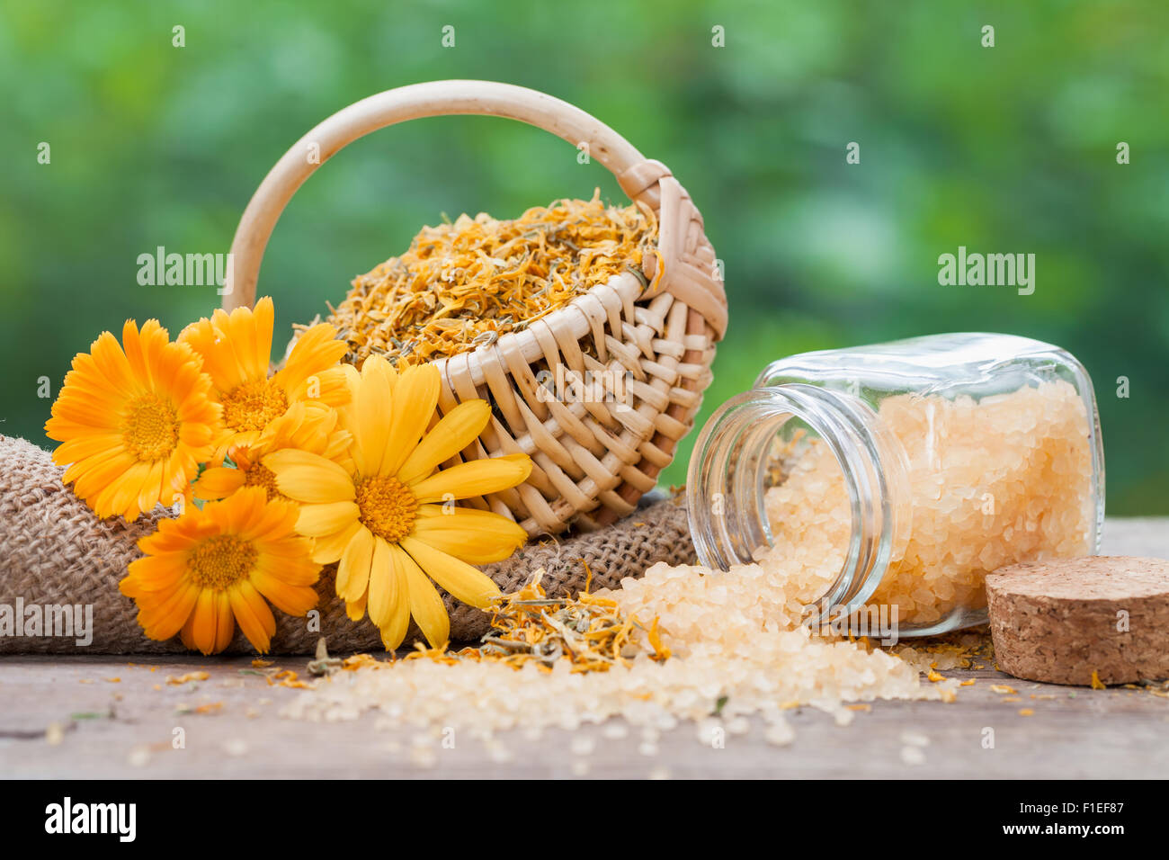 Marigold flowers, basket with dried plants and bottles of sea salt. - Stock Image