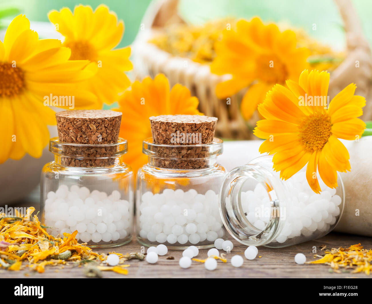 Three bottles of homeopathy globules and marigold flowers. - Stock Image