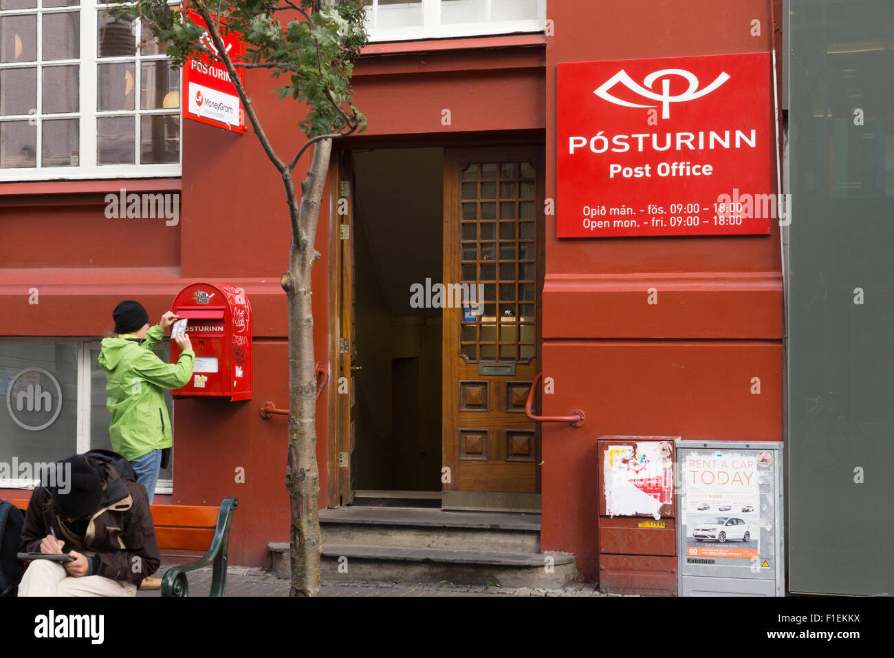 A female tourist posting postcards at the main post office in Reykjavik city centre - Stock Image