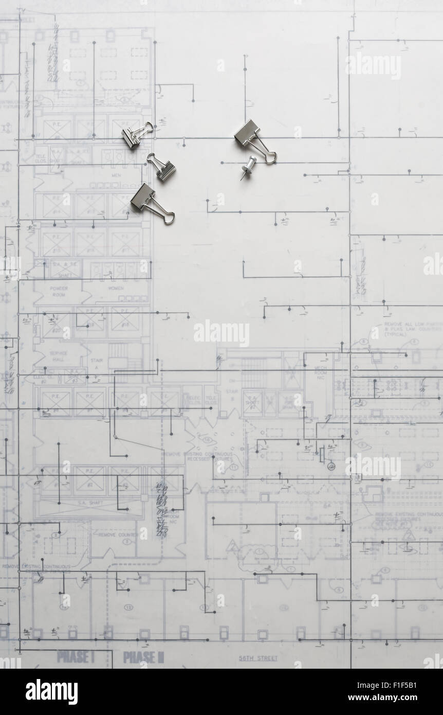 Still Life of blue print with push pins and binder clips. - Stock Image