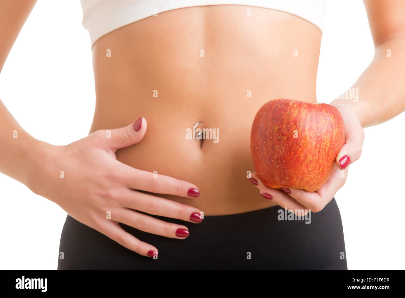 Woman holding an apple with a hand on her abdomen. Focus on the apple. - Stock Image