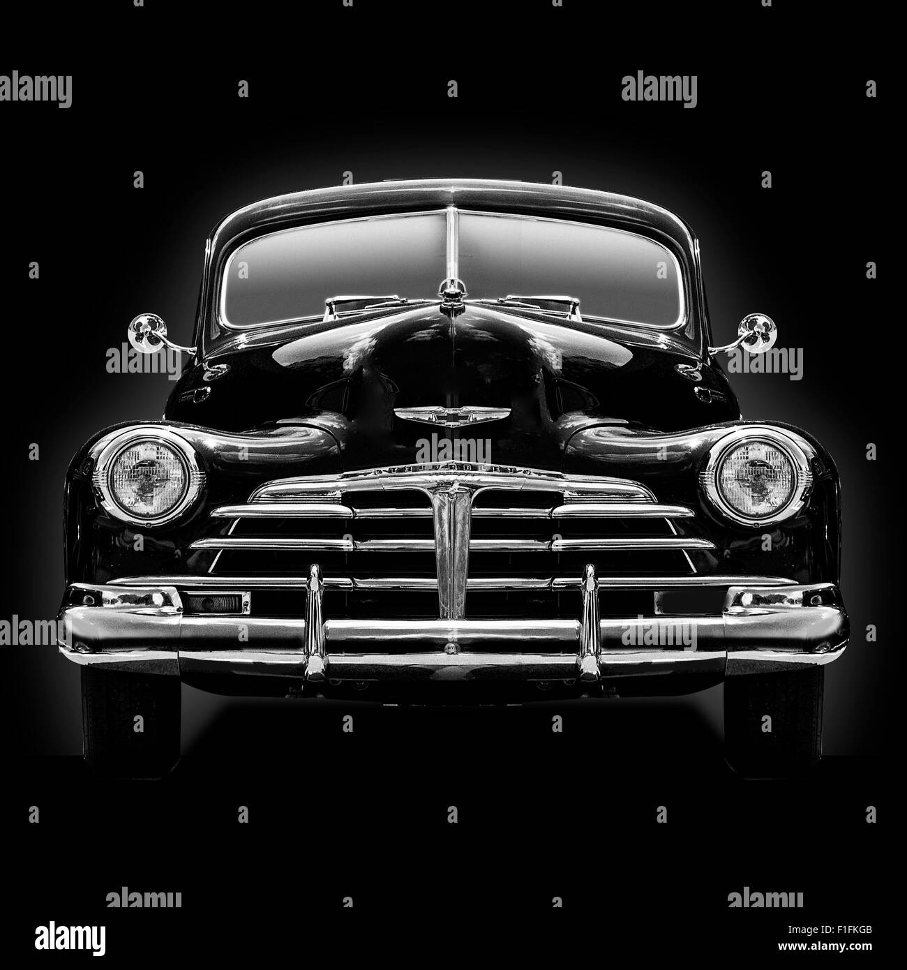 A b&w head on view of a 1950 Chevrolet Coupe knocked out on a black background square format image. Stock Photo
