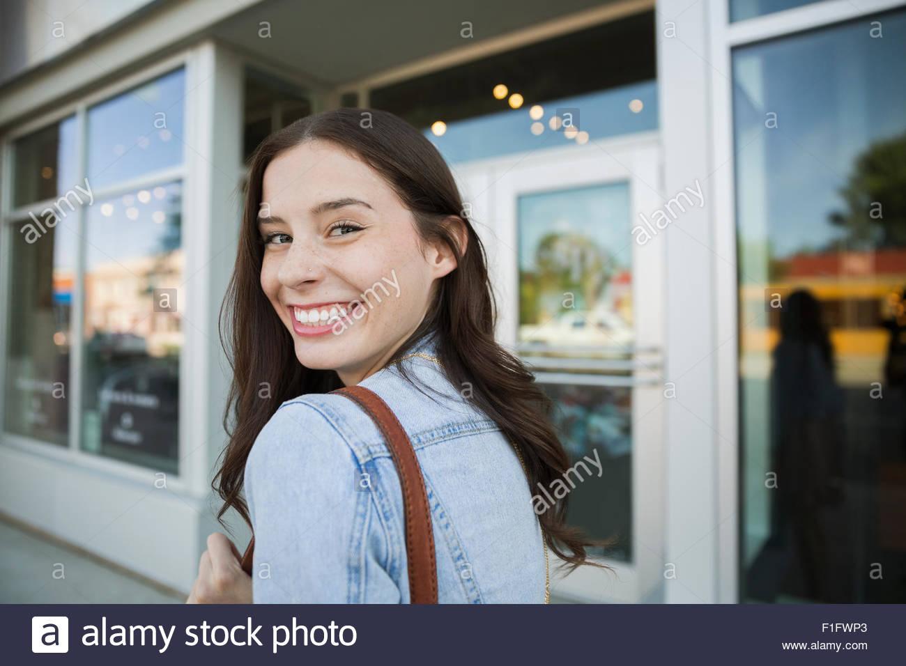 Portrait smiling brunette woman looking over shoulder - Stock Image
