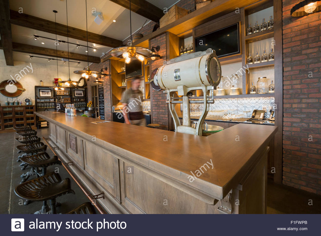 Worker walking behind counter at distillery bar - Stock Image