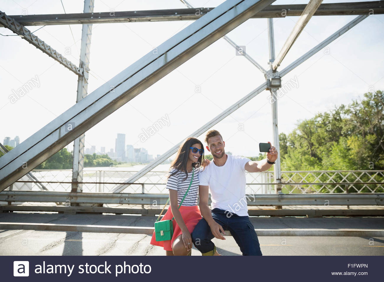 Couple taking selfie with camera phone sunny bridge Stock Photo