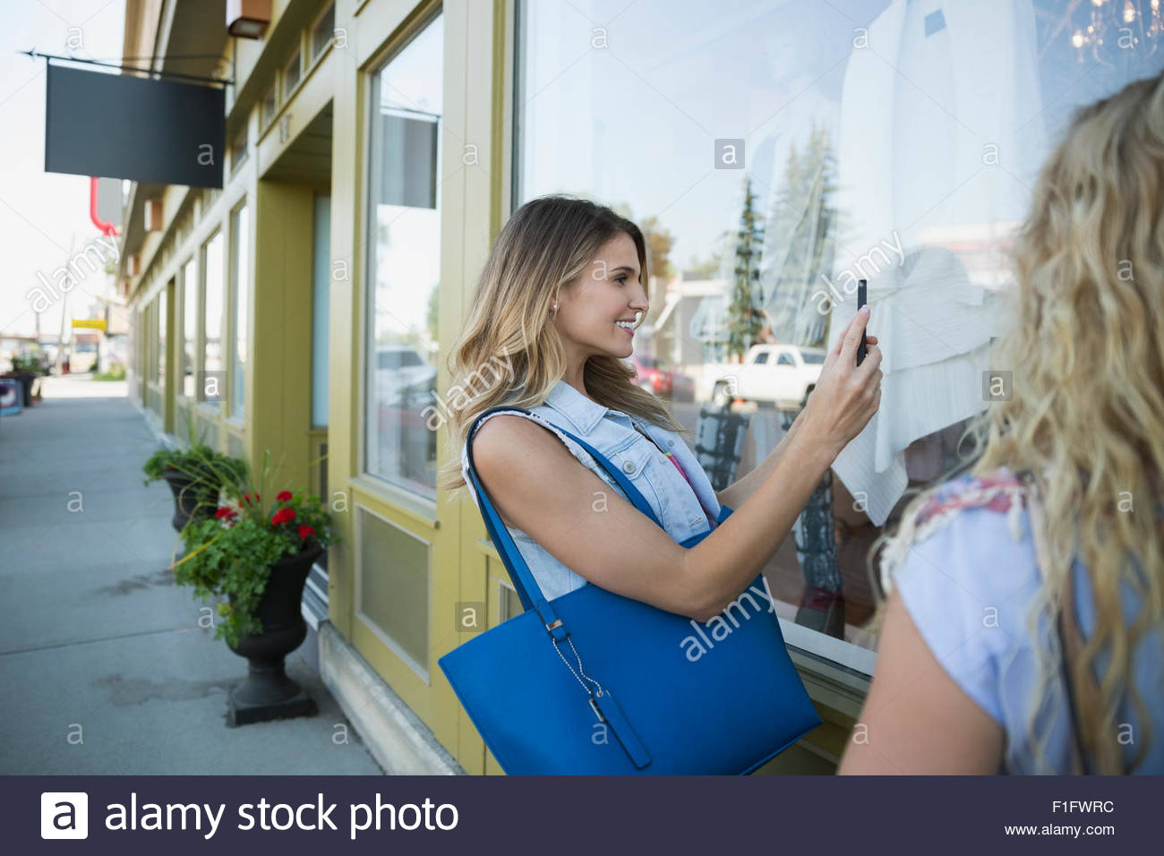 Woman photographing window display at storefront - Stock Image