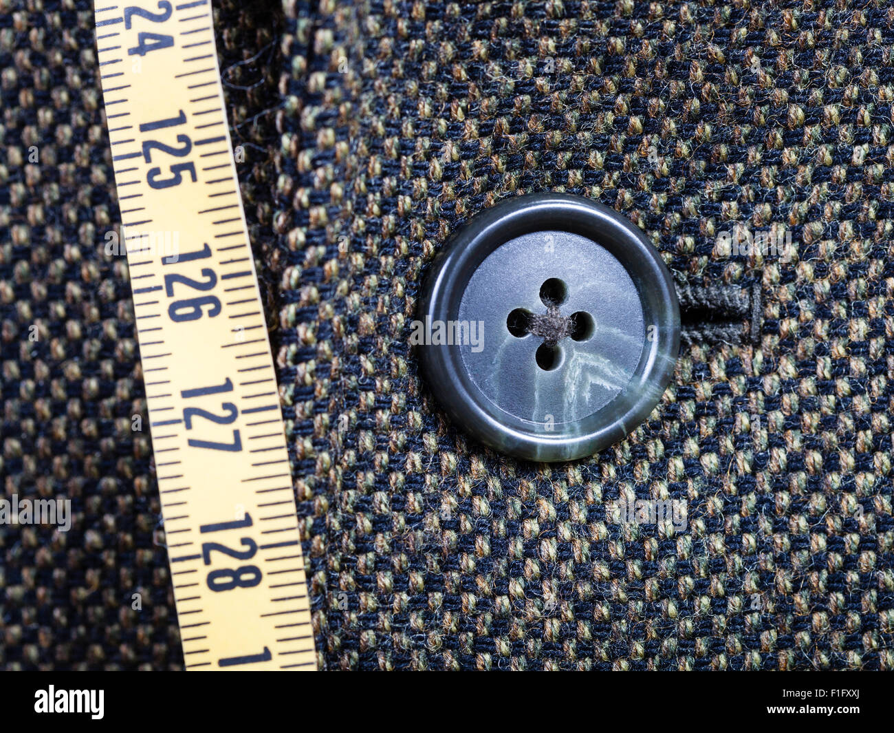 tailor measuring tape and buttoned button on tweed jacket close up - Stock Image