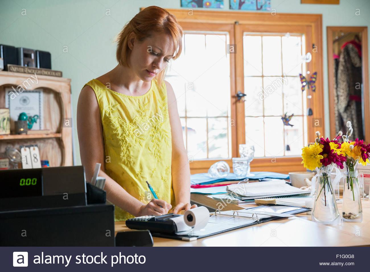 Shop owner paying bills at counter - Stock Image