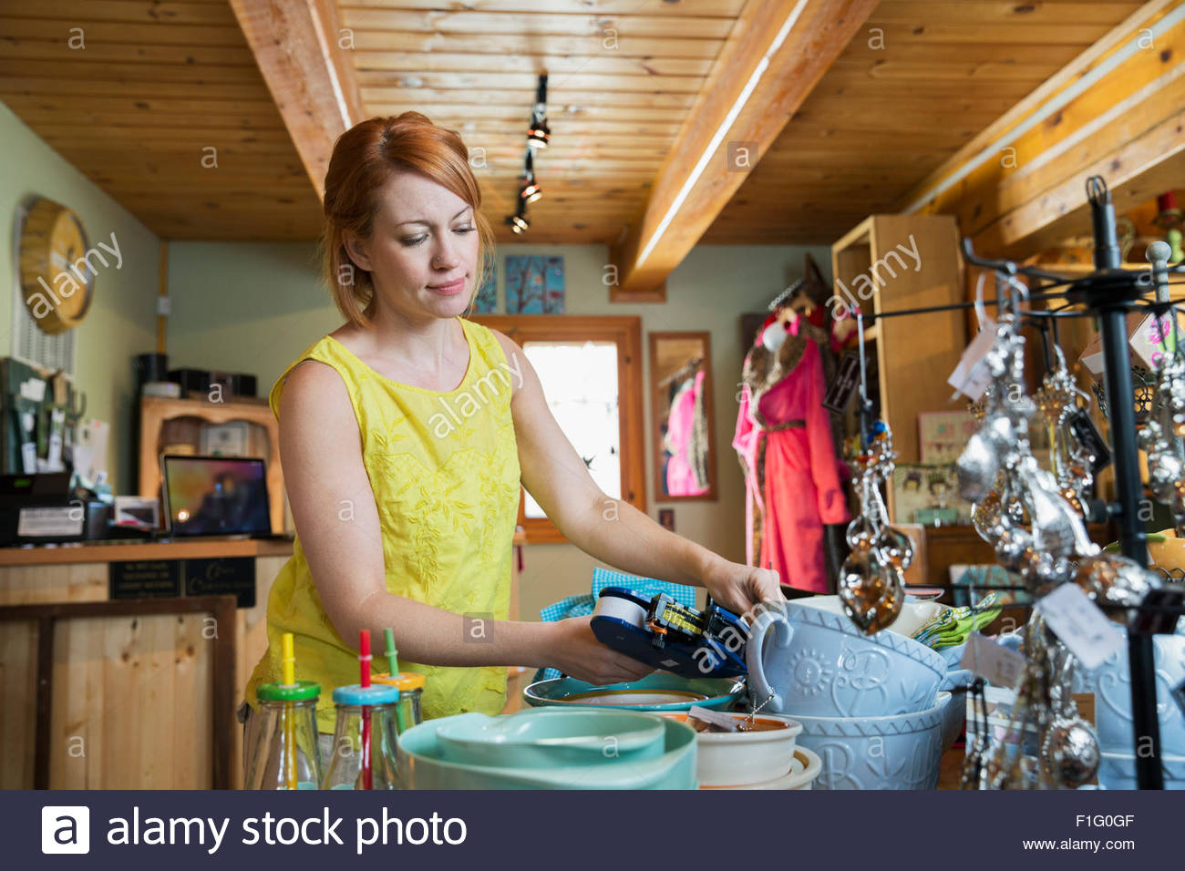 Shop owner tagging merchandise with price tags display - Stock Image